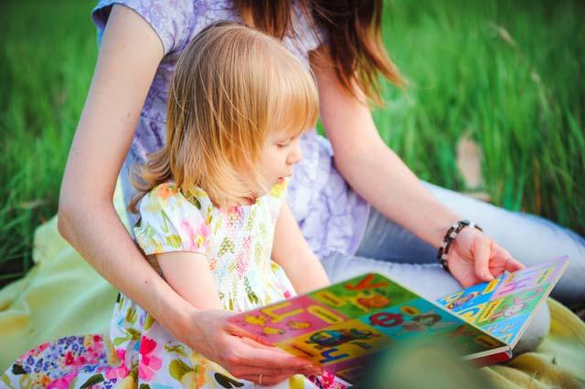 Mãe lendo livro com a filha
