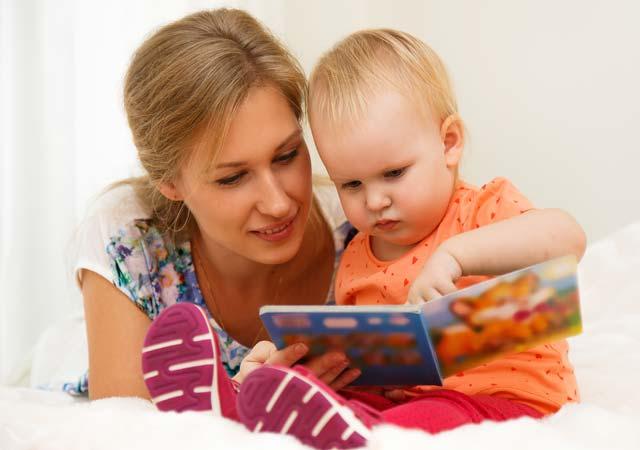 Mãe folheando livro com o bebê