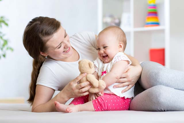 Mãe brincado com bebê sentado.