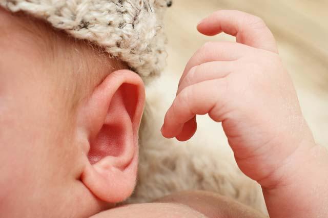 Bebê tocando ouvido com a mão